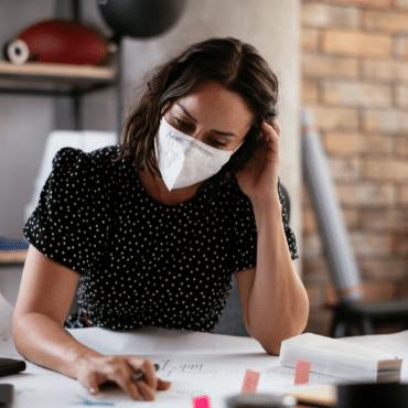 Woman at desk wearing mask